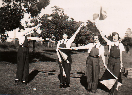 Ex-WRANs association of NSW, Dressed in the practical green uniforms designed by w:Florence Violet McKenzie, these Women's Emergency Signaling Corps members spell out W E S C with the semaphore flag signalling system, one of several signalling system
