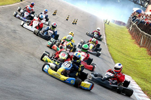 A pack of 10 go-karts entering a turn in a go-kart race