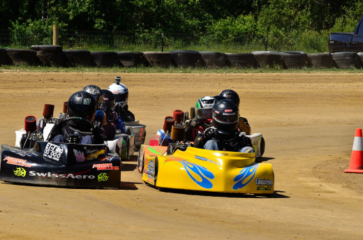 A pack of go-karts coming down double-file for a start of a flathead feature race