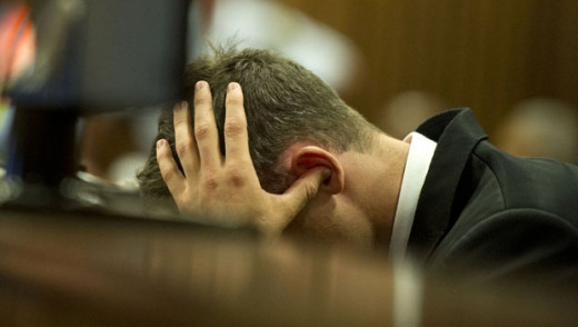 Oscar Pistorius covers his ears and lowers his head while the pathologist speaks to the court. Source: News 24