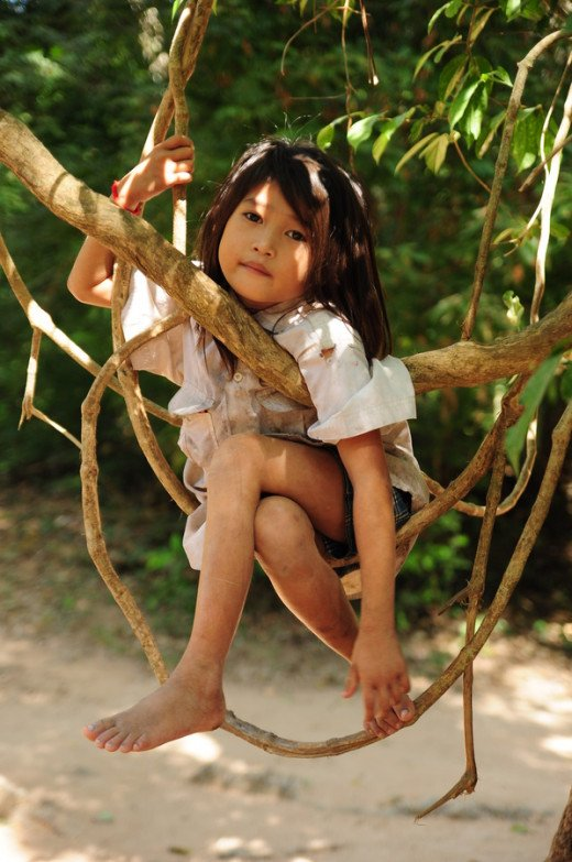 Show me the photo Photograph Little Girl sitting on a tree branch resting in Siem Reap, Cambodia by Anlun