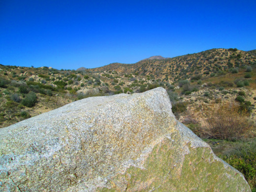 A boulder with  the view of the high desert.