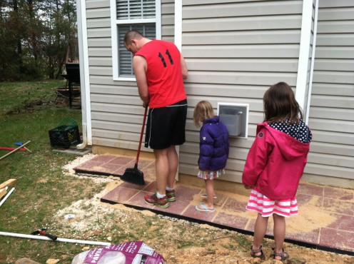 Sweeping and tamping sand into the cracks (note my daughters in short sun skirts and winter coats).