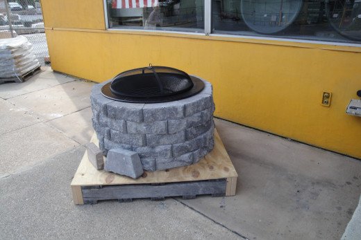 Showcasing the complete fire pit enclosure with samples of two paver sizes (in front).