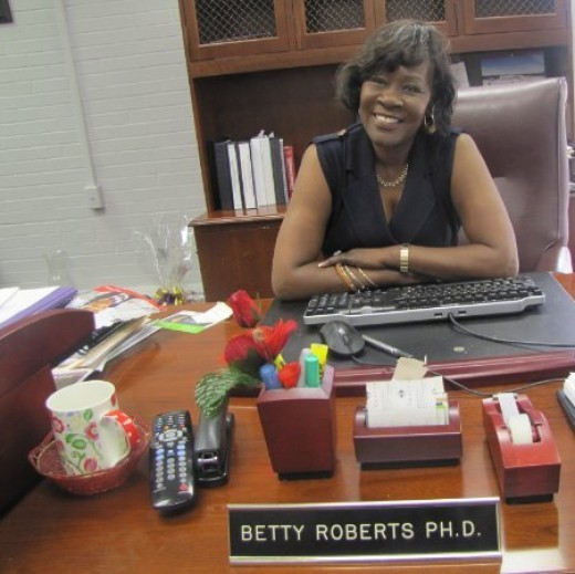 Dr. Betty J. Roberts smiles from across her desk as she carries out her duties as a senior administrator.