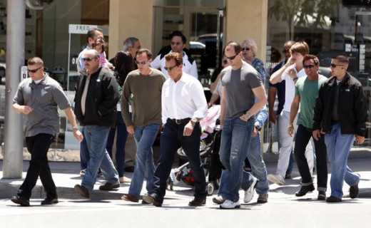(Above) Arnold Schwarzenegger and his personal assistants.  Celebrity PAs often work on location with their employers, which usually requires very  long hours.