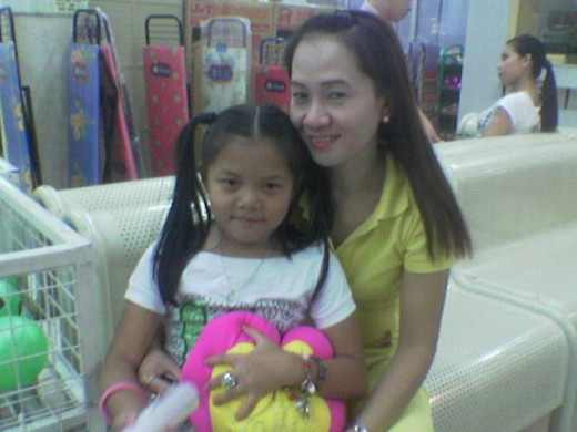 Pureza, Nurse, 42, with youngest daughter, Angel, 7,  Grade I