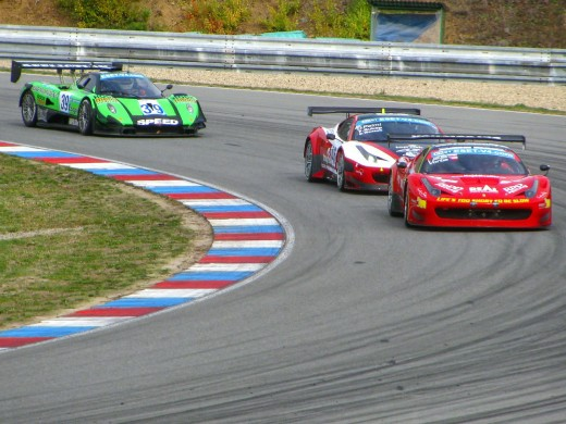 Two Ferrari F-458 Italia race-cars and a Pagada Zondi racing around a turn of a road-course track.