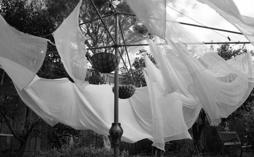 Dahliyani Briedis. White muslin sheets hanging on a washing line, blowing in the wind, in a backyard in Cheltenham, Victoria, Australia. Hanging baskets are also attached to the line.