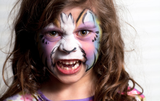 Girl with painted face acting a fierce part