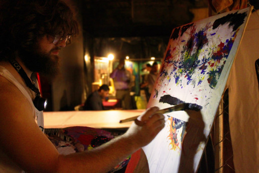 Artist Eric Alan works on a live painting next to the stage.