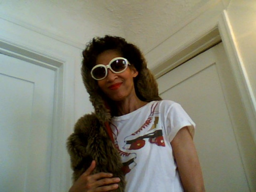 Victoria Moore in a vintage faux fur chubby coat, retro t-shirt and vintage shades.