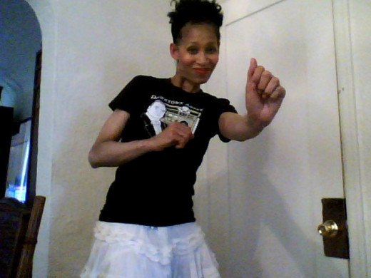 "Victoria Moore dancing in a black ""Downtown Abbey"" t-shirt and a white ruffly skirt from ""Goodwill Industries Thrift Store""."