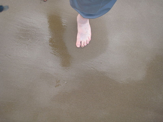 Blkutter, Foot stepping on wet sand causing sand to appear dry around the foot. Sand dilates due to the pressure of the foot nearby and draws water into pores so it appears to be dryer.