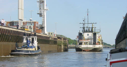 The Manchester Ship Canal at water level. A tug follows an ocean-going vessel at the port quarter