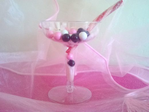 Assemble the candy pieces as if a drink had been poured into the glass. use the long candy piece as a cocktail straw, umbrella, or toothpick. Cotton candy gives the impression of dried ice or fluidity in the glass.