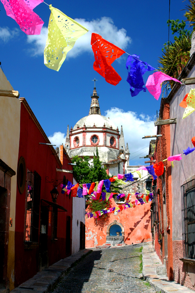 Brightly colored papel picados decorate the bright blue sky.
