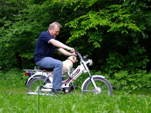 Photo by Vojko Kalan: Shows an older man riding a bike.