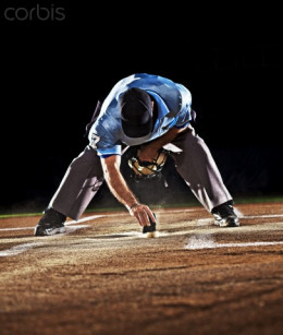 Home plate ump cleans home plate.