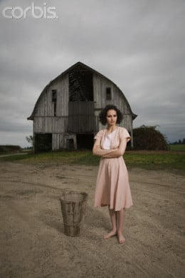 Woman stands in front of her antiquated barn