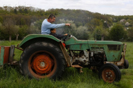 Some farmers teach their sons how to operate a tractor