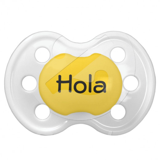 This cheerful baby pacifier has a cute Hola on a yellow background, perfect for Cinco De Mayo.