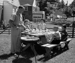A 50's family barbecue complete with the dad in long pants, loafers, and the kids all dressed appropriately