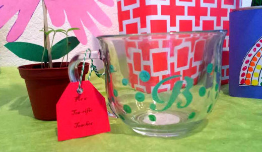 "Personalize a glass mug using glass paint.  Use a stencil to trace with if you don't want to use free hand.  I added the dots with the eraser tip of a pencil.  Attach a tag that says, ""For a Tea-rific Teacher."""