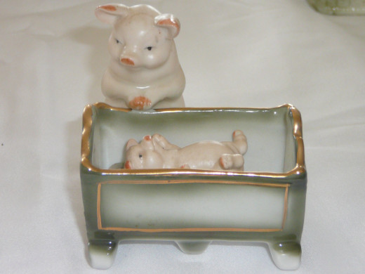"Momma with baby pig in cradle. Featured in ""This little Piggy"" its '92 value was $190. 3 1/4"" x 3 1/4"". Paid $48. Common."