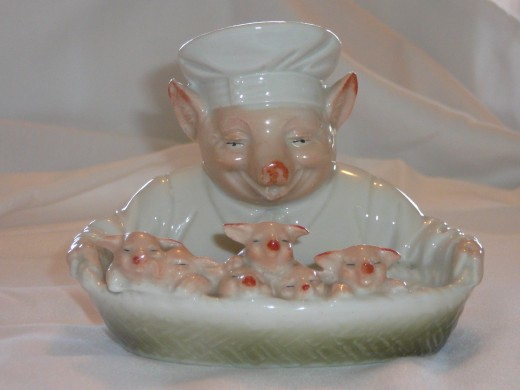 "This amazing chef is holding a basket with 6 little pigs"" Featured in ""This little Piggy"" its '92 value was $475. I've only seen it come up on ebay twice. 5"" x 4"" Paid $313. Rare."