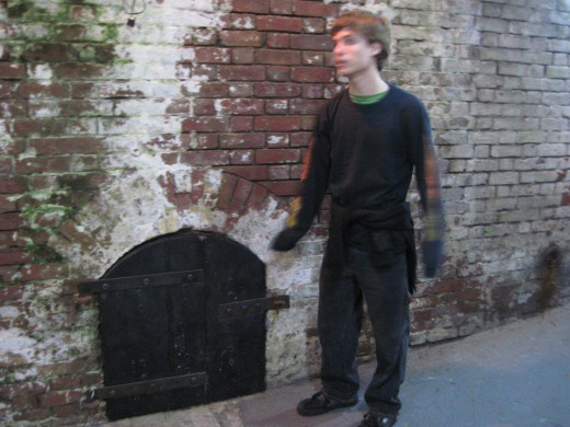 Elder son standing beside a tiny mysterious wooden door in the main tunnel.