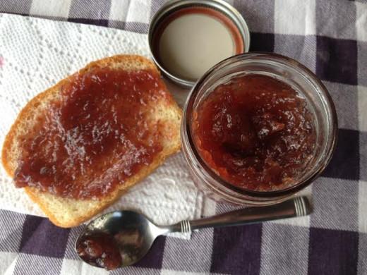 Homemade raspberry preserves on a slice of homemade bread.