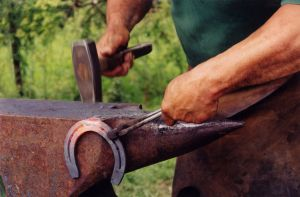 A blacksmith with horse shoe