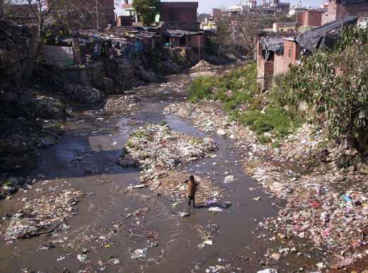 Garbage filled river flowing across a slum