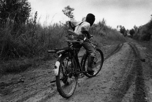 A child soldier rides to his base.