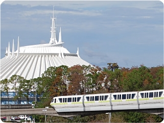 A monorail passes by with Space Mountain in the background.