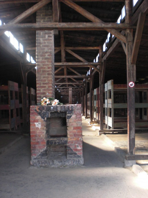 Men's barracks interior. Wooden beds share the function of filing cabinets and often slept four bodies per level. The foreground displays one of two fireplaces per barracks.