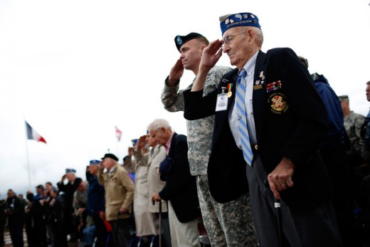 World War II vets, members of the 29th Infantry Division who landed at Omaha Beach salute during the playing of the U.S. national anthem at a ceremony honoring the division's sacrifices June 4 in Vierville-Sur-Mer, France.