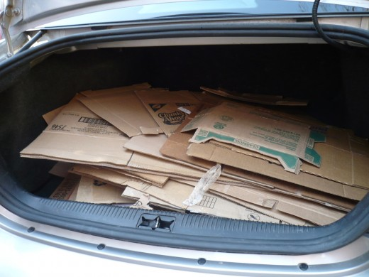 The car trunk is full of cardboard for the garden