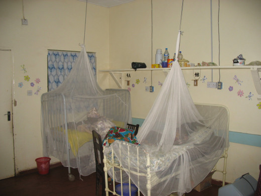Two beds in pediatric ICU at ECWA Evangel Hospital, Jos, Nigeria. Beds are covered with mosquito nets. A mother is sitting, sleeping, under the far net.