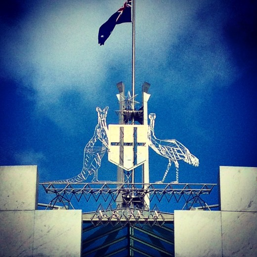 Close-up of the Australian Flag and Coat of Arms atop the Parliament House