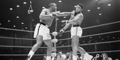Muhammad Ali is seen with his hands down dodging a jab from Sonny Liston.