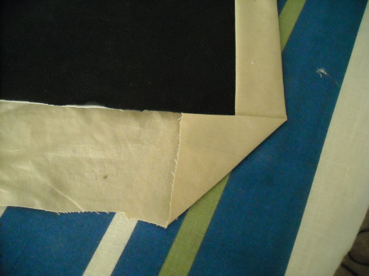 Position the quilt so that the exposed raw edge is towards you. Bring the bottom right corner and bring it up so that it is touching the raw edge of the quilt top. It should form a right triangle. Press