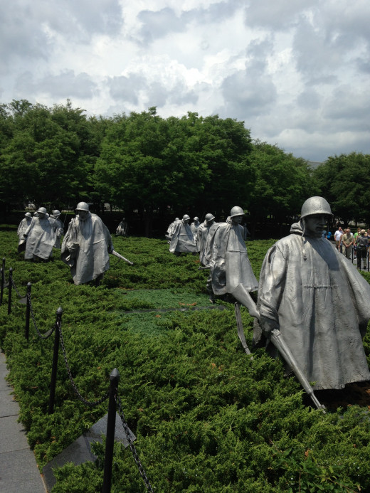 SQUAD OF KOREAN VETS MOVING THROUGH THE FIELD
