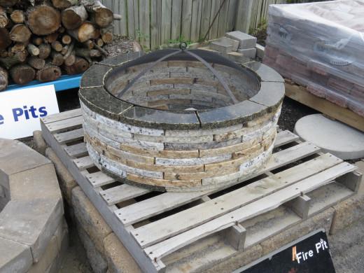 Granite fire pit surround with spark arrestor screen.