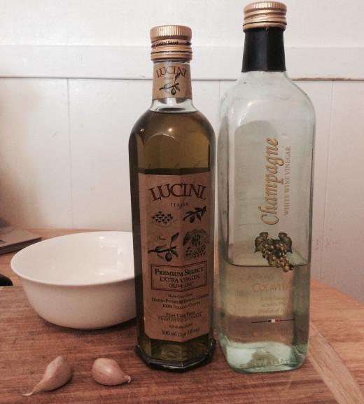 Dressing ingredients (olive oil, vinegar, garlic cloves)