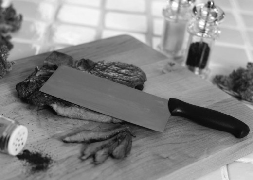 Sirloin skillet steak sliced on wooden cutting board with cleaver.