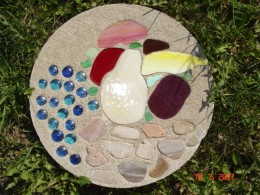 Cement stepping stone inlaid with stained glass, glass beads and pebbles.