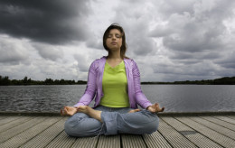 Woman doing meditation in the yoga posture known as full lotus, lotus pose or lotus position. Her left knee is supposed to be resting on the floor.