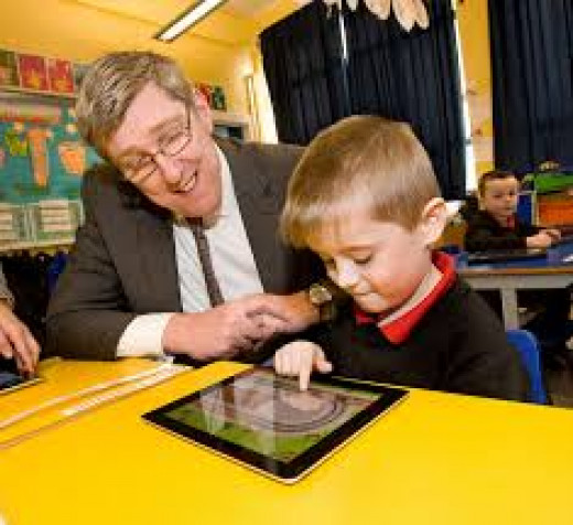 Education Minister pictured with pupil Cormac Wilkinson during his visit to Holy Cross Boys' Primary School in Ardoyne